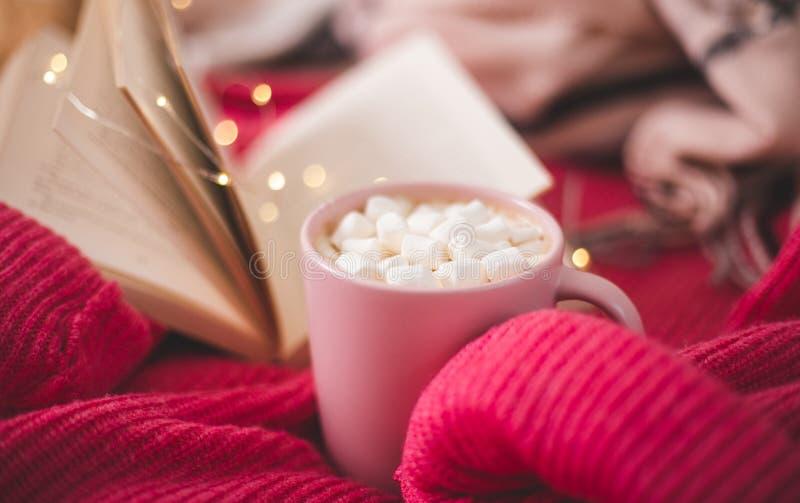 Rosa Tasse Kaffee mit Marschmelze und offenes Buch über Weihnachtslichter auf dem gestrickten, leuchtend roten Pullover Hintergru stockfotos