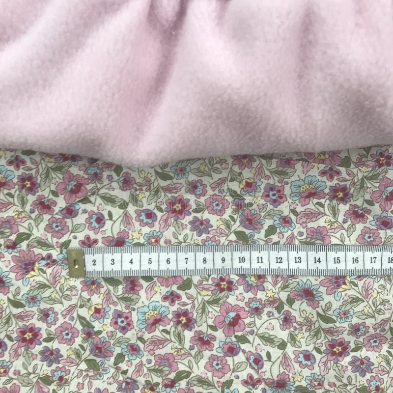 Rosa textil på blommaprintetbomull och måttband arkivbilder