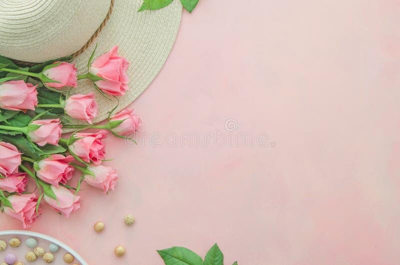 Rosa Tischplattenarbeitsplatzkonzept der Draufsichtsommerfrauen mit einem Strohhut, Bonbons und rosa rosafarbenen Blumen Kopieren stockfoto
