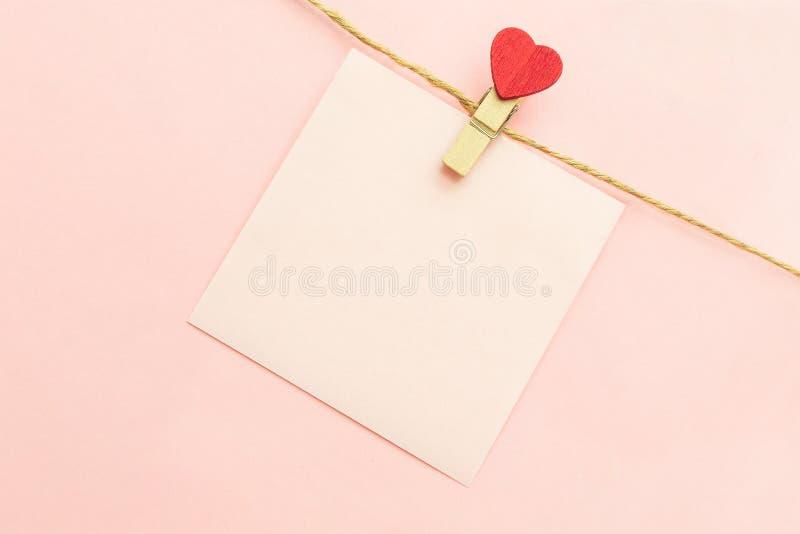 Rosa tomt pappers- ark på en kläderlinje och klädnypor med röd hjärta på en rosa bakgrund hjärta för gåvan för dagen för begreppe royaltyfria bilder