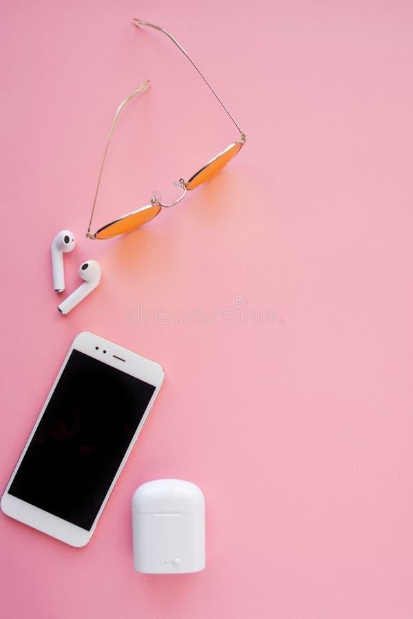 Rosa transparente Sonnenbrille, drahtlose Kopfhörer und Smartphone liegen auf einem rosa Hintergrund stockfotos
