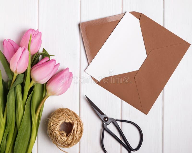 Rosa tulpan och kuvert med tom papr på den vita träfliken royaltyfri foto