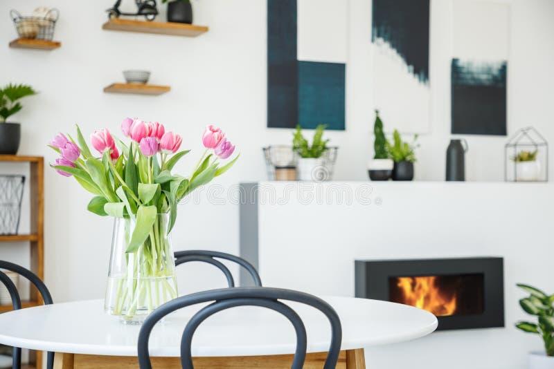 Rosa tulpan på att äta middag tabellen i inre för vitt rum med växter a arkivbild