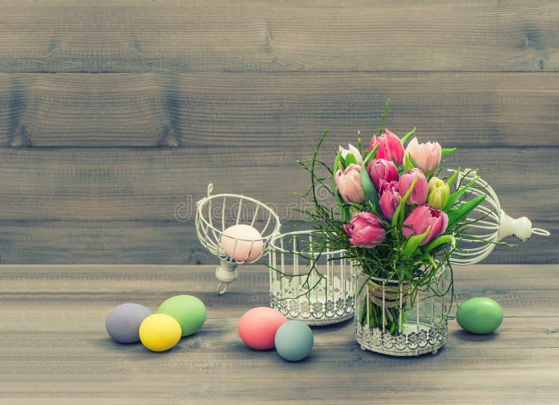 Rosa tulpanblommor och easter ägg. tappningstil arkivbilder