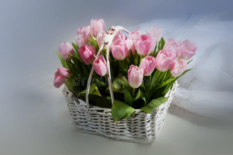 Rosa Tulpen im Korb mit Eheringen stockfoto