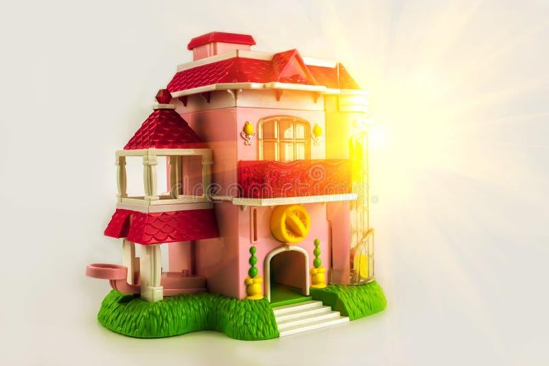 Rosa två-våning stuga med en gräsmatta nära huset på solnedgången Till royaltyfria foton