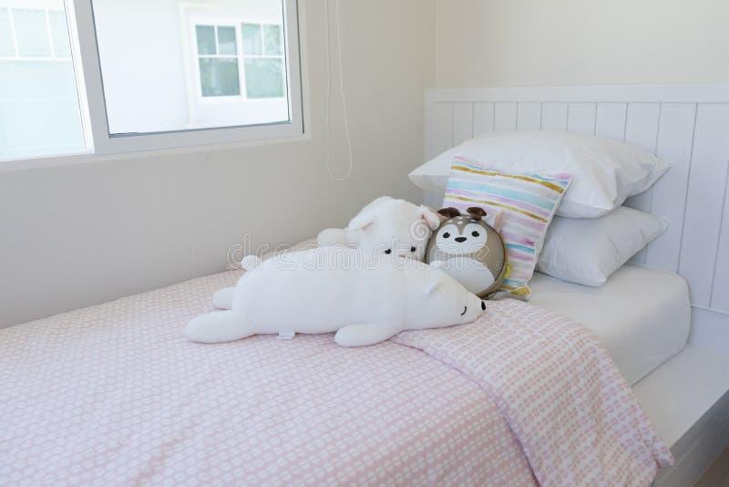 Rosa und blaue Decke mit kreativen Kissen auf Bett im bunten Kinderraum lizenzfreies stockfoto