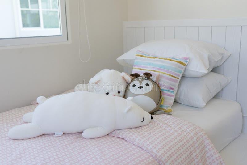 Rosa und blaue Decke mit kreativen Kissen auf Bett im bunten Kinderraum lizenzfreie stockfotos