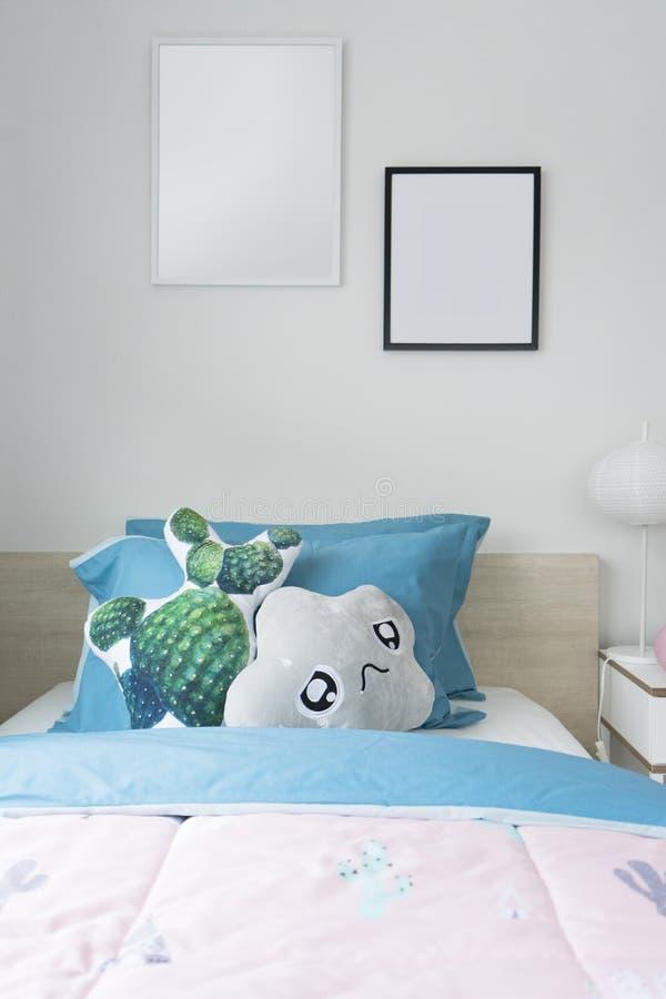 Rosa und blaue Decke mit kreativen Kissen auf Bett im bunten Kinderraum stockfoto