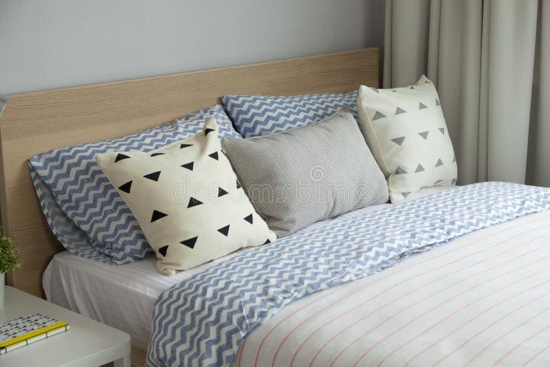 Rosa und blaue Decke mit kreativen Kissen auf Bett im bunten Kinderraum stockbild