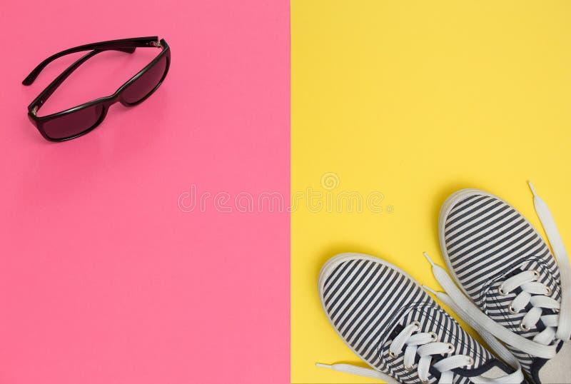 Rosa und gelber Hintergrund mit Sonnenbrille und gestreiften Schuhen, SU stockfotografie