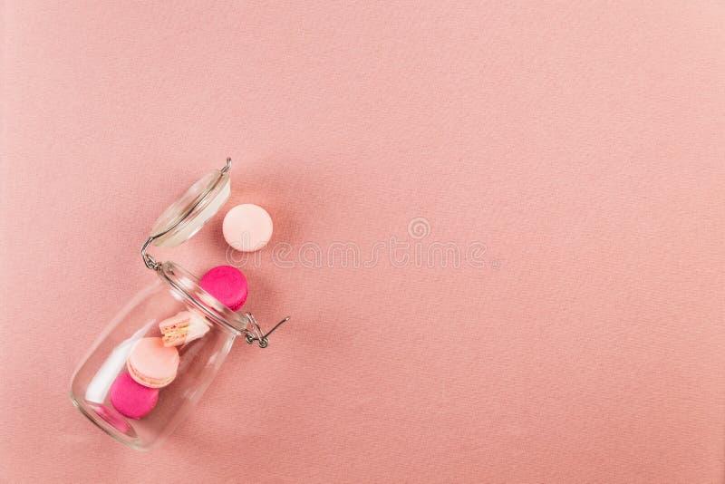 Rosa und magentarote französische macarons oder Makronen, fallend aus einem Glasgefäß über einem rosa Tischdeckenhintergrund mit  lizenzfreies stockfoto