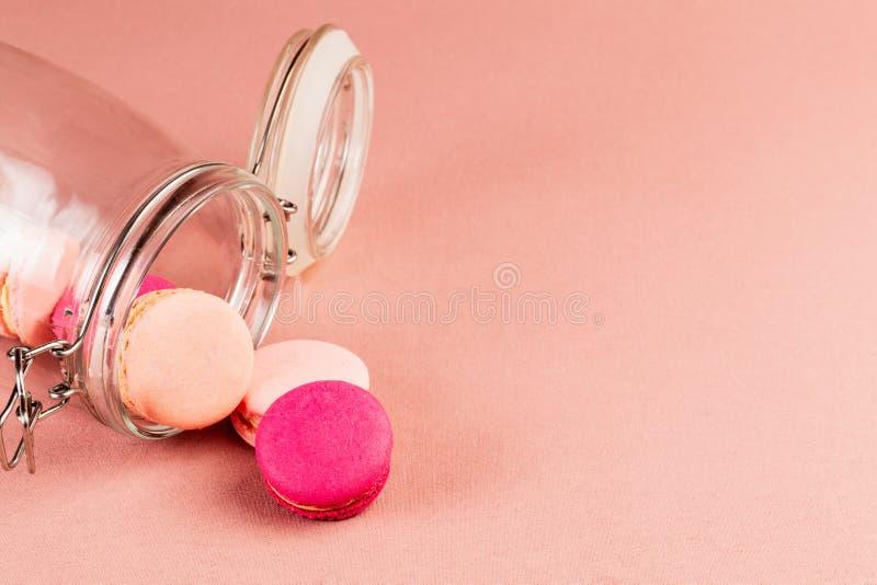 Rosa und magentarote französische macarons oder Makronen, fallend aus einem Glasgefäß über einem rosa Tischdeckenhintergrund mit  lizenzfreie stockfotos
