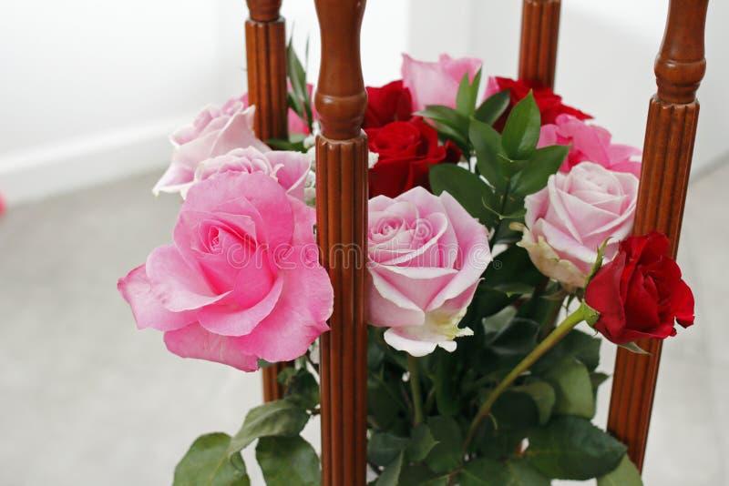 Rosa und rote Rosen-Anordnung mit Holz stockfoto