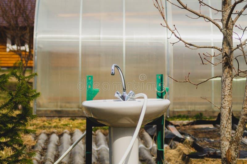 Rosa und Wasserhahn im Garten Wasserhahn außerhalb des Hauses Hinterhof des Sommerhauses naturnahes Konzept stockfotografie