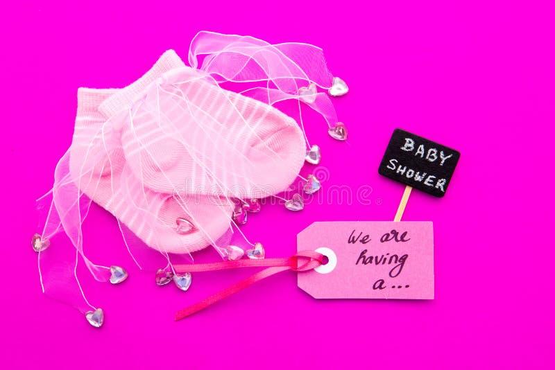 Rosa und weiße Socken des Babys - auf rosa Hintergrund mit Aufkleber - wir ` bezüglich des Habens eines Mädchen- und Babypartytaf lizenzfreie stockfotografie