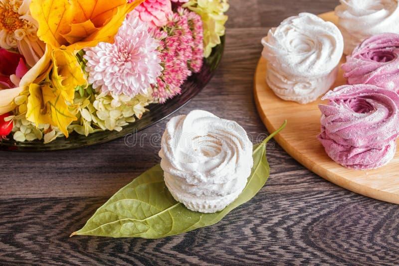Rosa und weißer Eibischzefir auf ein runden hölzernes Brett wi stockfoto