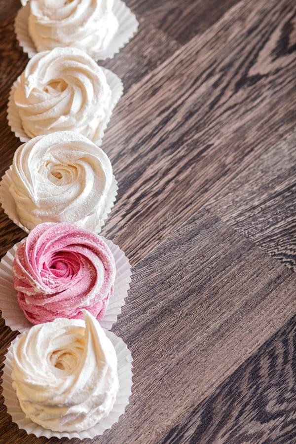 Rosa- und weißeselbst gemachte Eibische auf einem grauen hölzernen Hintergrund lizenzfreie stockfotografie