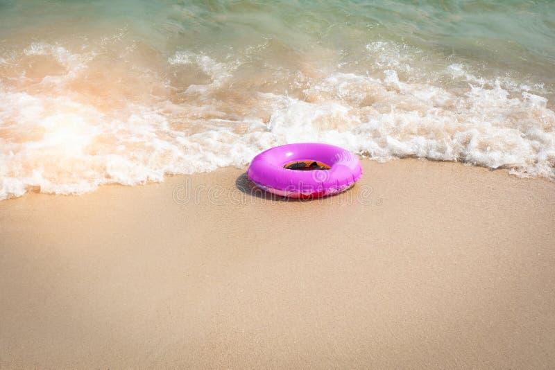 Rosa uppblåsbar gummiring på stranden i ytligt vatten royaltyfri fotografi