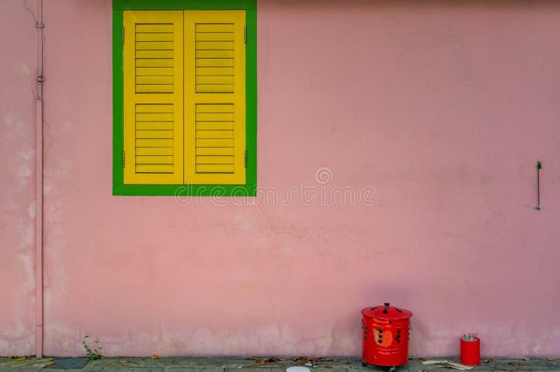 Rosa vägg med den gröna ramen av fönstret med gula slutare royaltyfri bild
