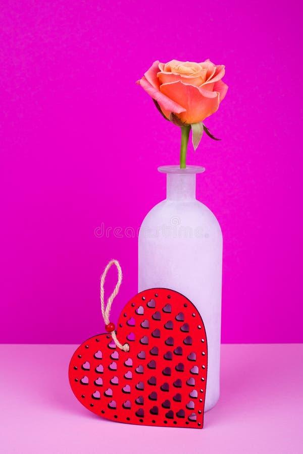 Rosa in vaso, cuore di legno su fondo rosa immagine stock libera da diritti