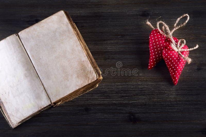 Rosa vermelha Corações feitos a mão de pano vermelho e livro aberto velho no fundo de madeira imagens de stock