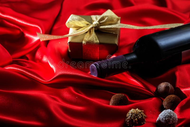 Rosa vermelha Garrafa de vinho tinto, chocolates e um presente no cetim vermelho fotografia de stock