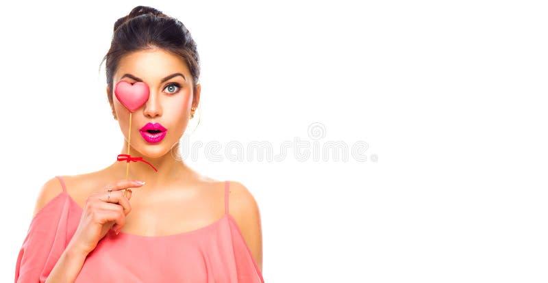 Rosa vermelha Menina nova alegre do modelo de forma da beleza com a cookie dada forma coração do Valentim em sua mão imagens de stock