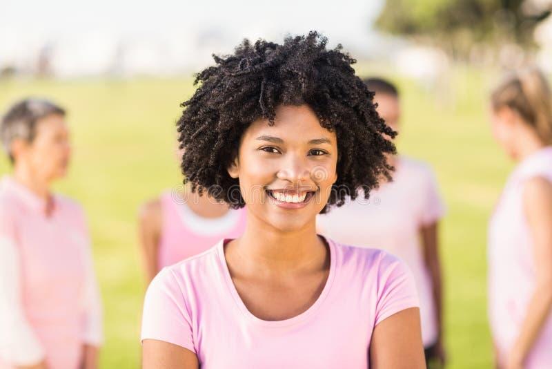 Rosa vestindo de sorriso da jovem mulher para o câncer da mama na frente dos amigos foto de stock royalty free