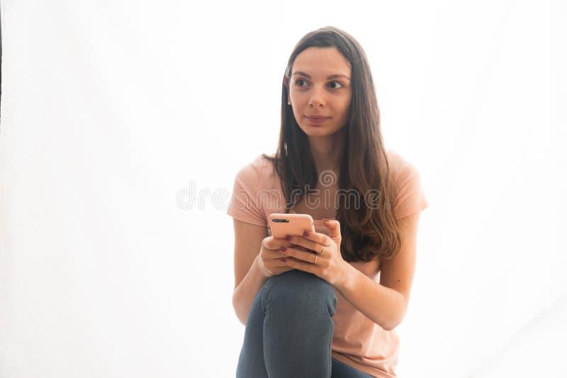 Rosa vestindo e calças de brim da jovem mulher usando o telefone no caso cor-de-rosa, influencer social dos meios imagens de stock royalty free