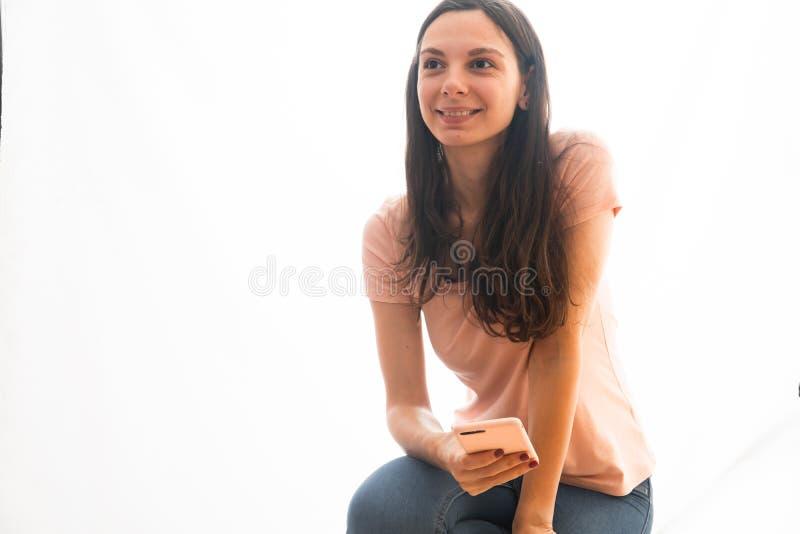 Rosa vestindo e calças de brim da jovem mulher usando o telefone no caso cor-de-rosa, influencer social dos meios imagem de stock royalty free