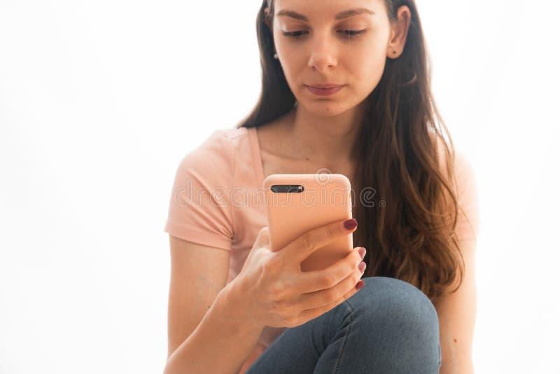 Rosa vestindo e calças de brim da jovem mulher usando o telefone no caso cor-de-rosa, influencer social dos meios foto de stock royalty free