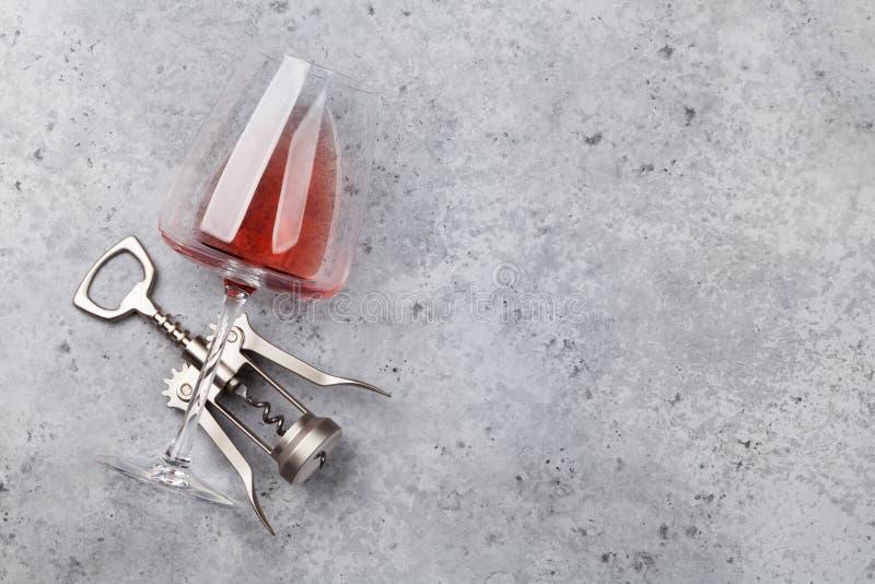Rosa vinexponeringsglas och korkskruv arkivfoto
