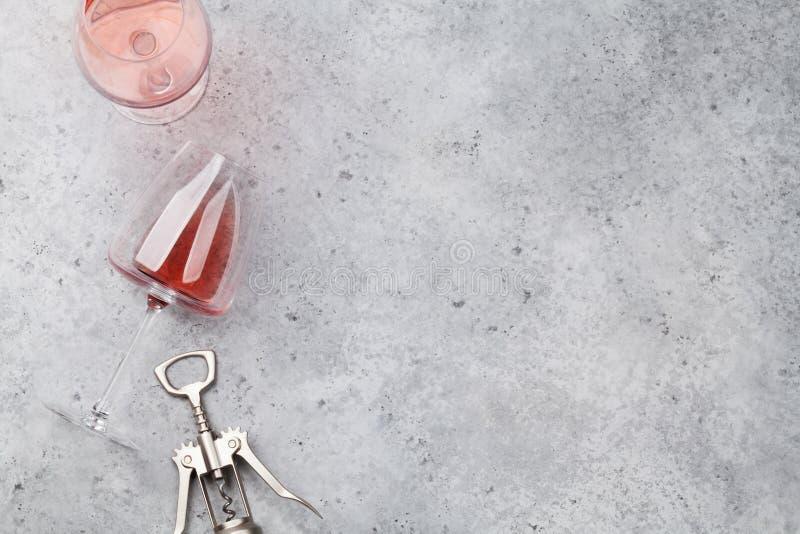 Rosa vinexponeringsglas och korkskruv royaltyfri bild