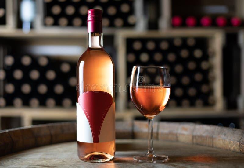 Rosa vinflaska med en fylld vinglas på en trumma i en källare royaltyfri fotografi