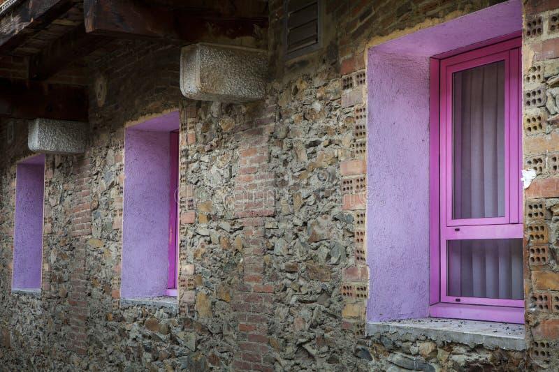 Rosa violet för tre fönster av ett hus som göras av stenar och tegelstenar arkivfoton