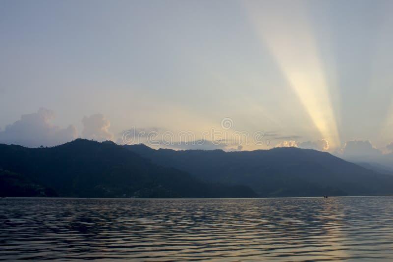Rosa vita linjer av solnedgångsolljus i den blåa himlen ovanför konturerna av bergen och sjön arkivfoto