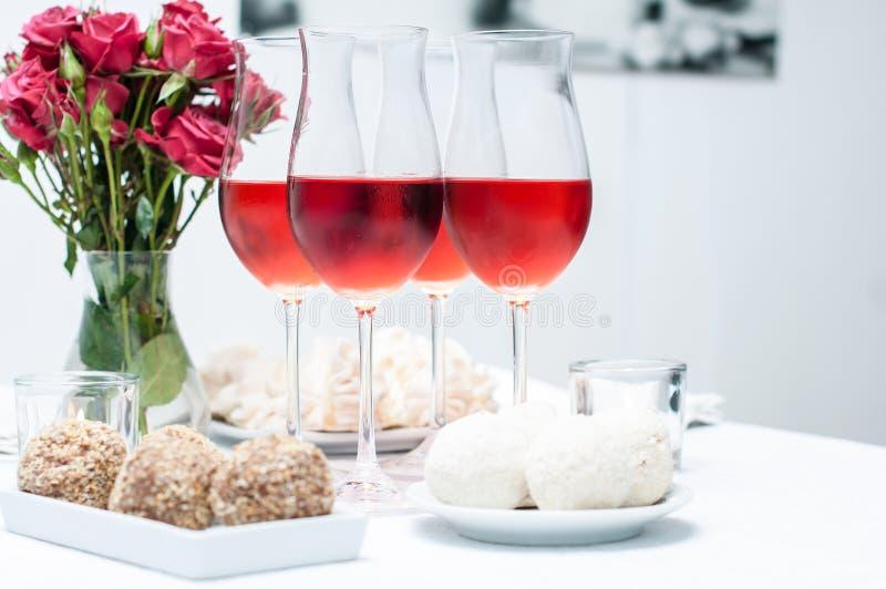 Rosa wine i exponeringsglas, hemparti arkivfoton
