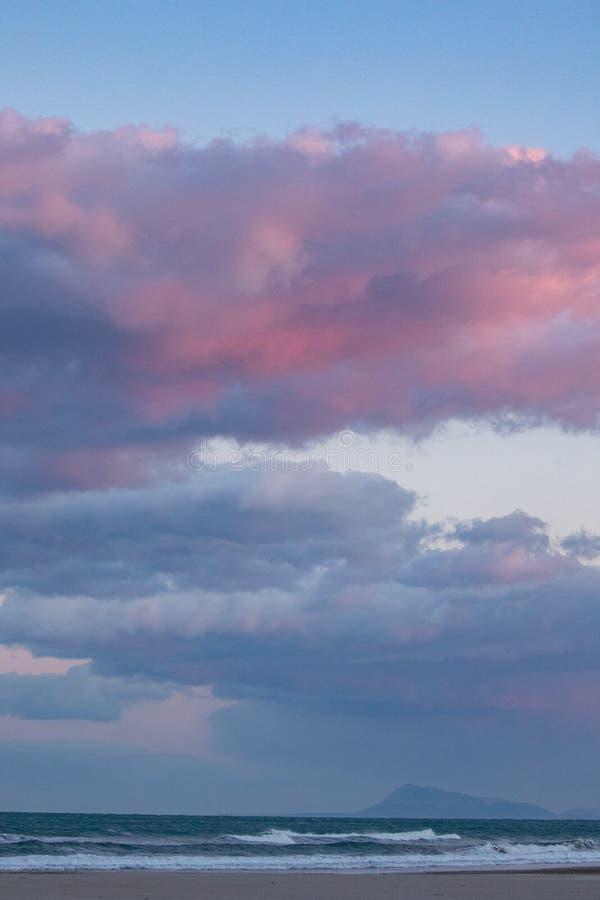 Rosa Wolken Dromatic über dem Meer mit Bergen im Hintergrund Sonnenuntergangszene in Spanien stockfoto