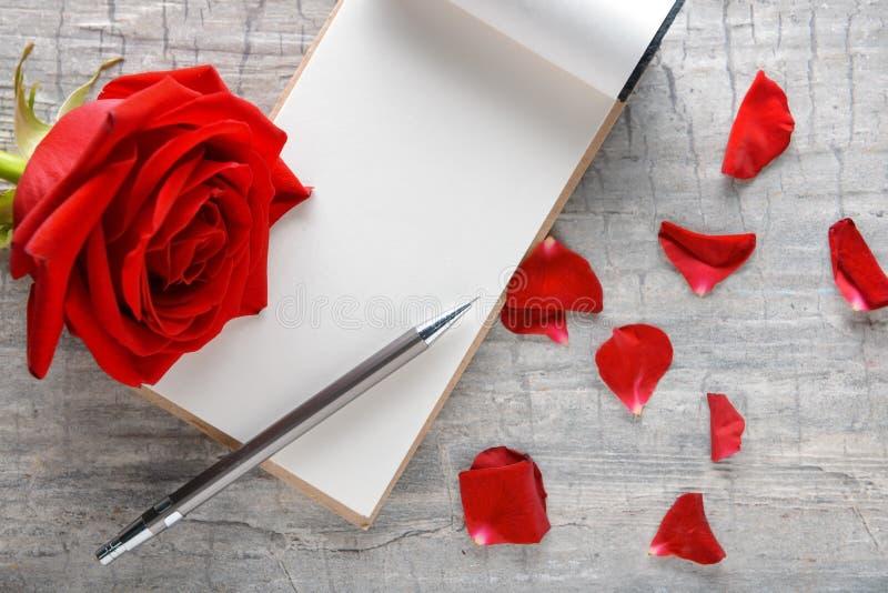 Rosa y cuaderno rojos hermosos en fondo de madera fotografía de archivo