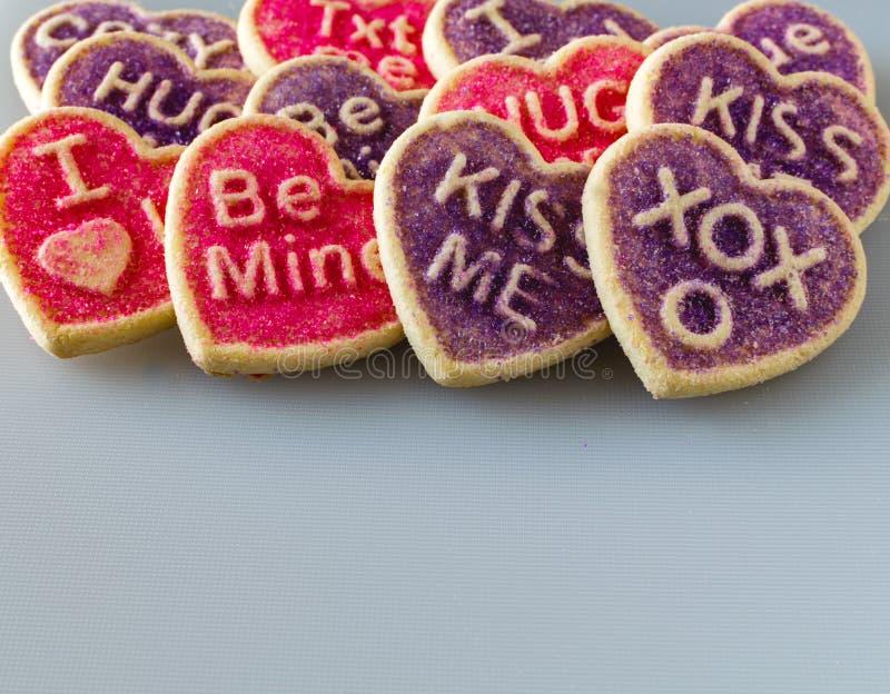 Rosa y galletas en forma de corazón púrpuras del ` s de la tarjeta del día de San Valentín de la conversación fotos de archivo