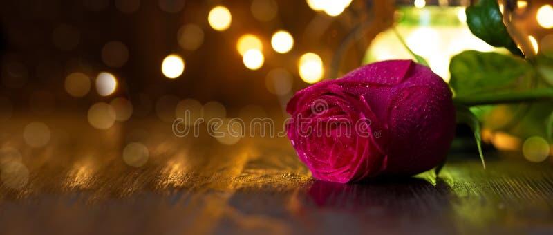 Rosa y linterna rojas con las luces en una tabla de madera fotos de archivo