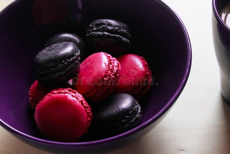Rosa y pastas púrpuras de las galletas en una placa y una taza de café imagenes de archivo