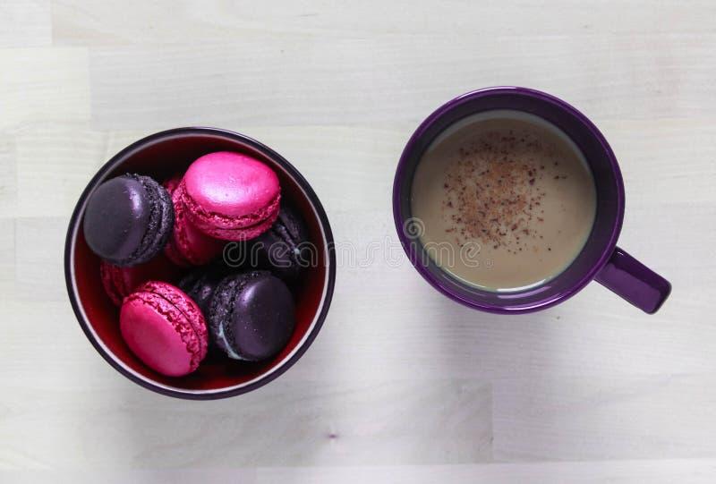 Rosa y pastas púrpuras de las galletas en una placa y una taza de café foto de archivo
