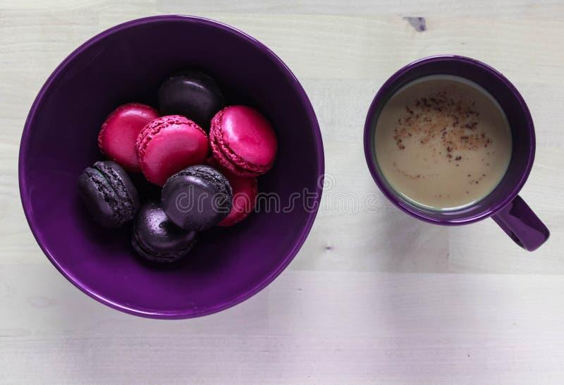 Rosa y pastas púrpuras de las galletas en una placa y una taza de café fotografía de archivo