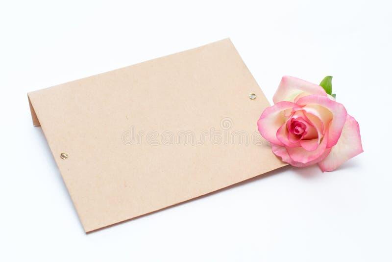 Rosa y sobre rosados en un fondo blanco, un sobre para la inscripción foto de archivo