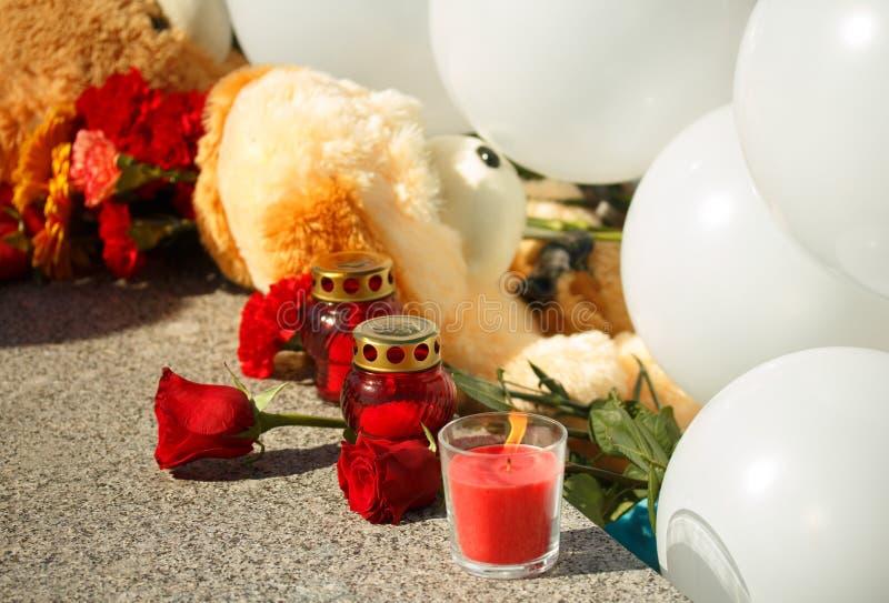 Rosa y vela del rojo Recuerde de terror de las víctimas imagen de archivo libre de regalías