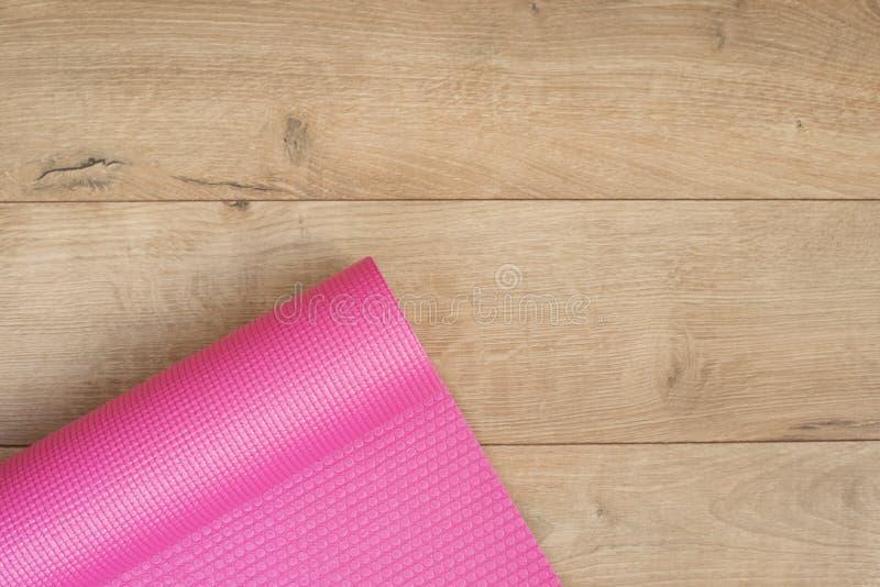Rosa Yogamatte auf einem hölzernen Hintergrund Eignungskonzept, aktiver Lebensstil, Körperpflegekonzept Hölzerner Hintergrund lizenzfreie stockfotografie