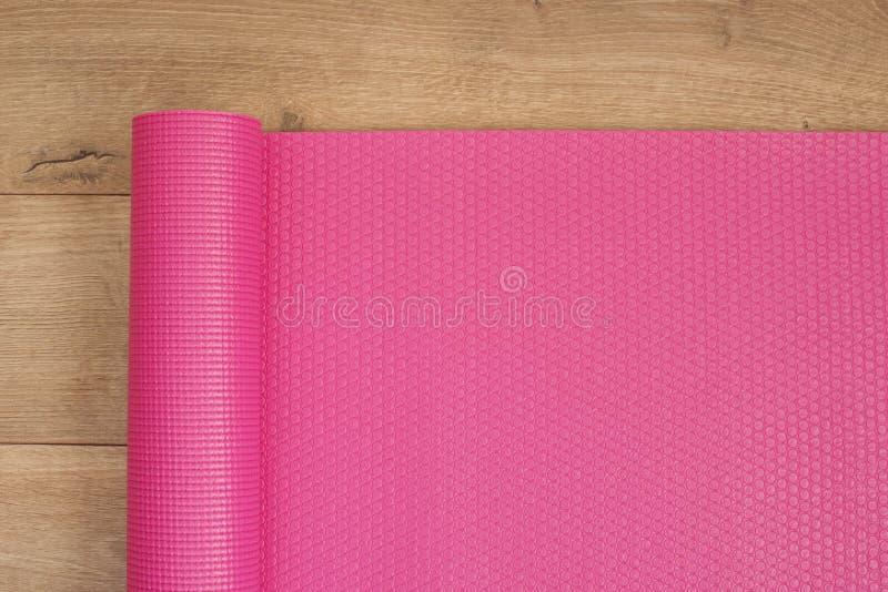 Rosa Yogamatte auf einem hölzernen Hintergrund Eignungskonzept, aktiver Lebensstil, Körperpflegekonzept Hölzerner Hintergrund lizenzfreie stockbilder