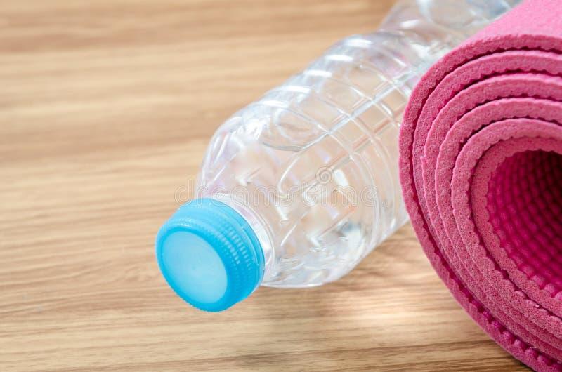 Rosa Yogamatte und eine Flasche Wasser lizenzfreies stockbild